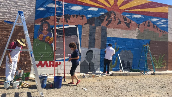 Phoenix community members work on the mural celebrating Latino history near Seventh Streetand Portland Avenue in downtown Phoenix on May 27, 2017.