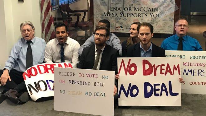 Protesters sit in front of the office door at Sen. John McCain's office in Phoenix on Dec. 4, 2017.