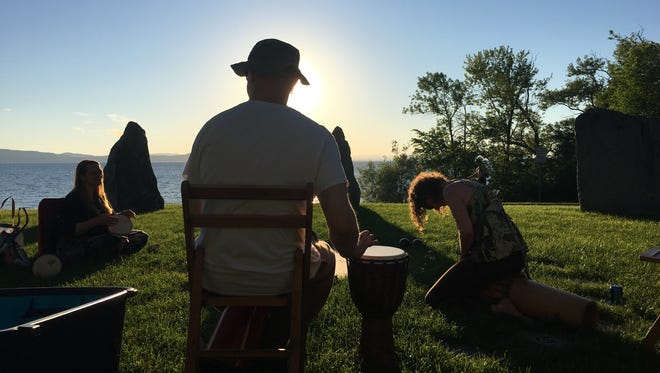 Michael Wojcik, center, of Charlotte, drums at the Earth Clock in Burlington as the sun sets over Lake Champlain. Wojcik is joined by Jeanette Bacevius of Shelburne, left; and Gyan Devi of Burlington, on Tuesday, June 19, 2018.