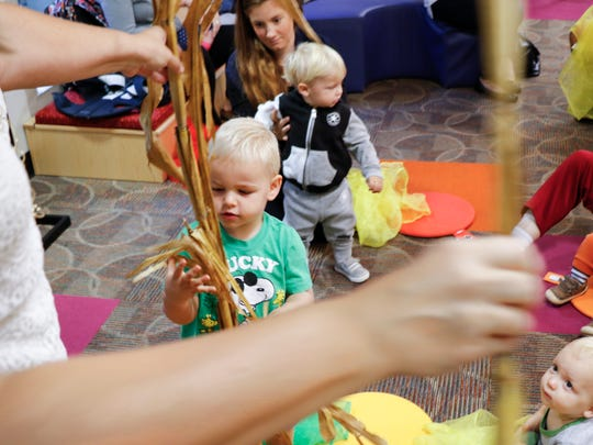 Bear Kerfgen, 2, of East Lansing, touches a cornstalk during story time at the East Lansing Public Library Monday, Oct. 9, 2017.  Youth Services Specialist Tracey Pickard read them a book to celebrate the second annual Indigenous People's Day in East Lansing. City Council voted last year to recognize the holiday instead of Columbus Day.