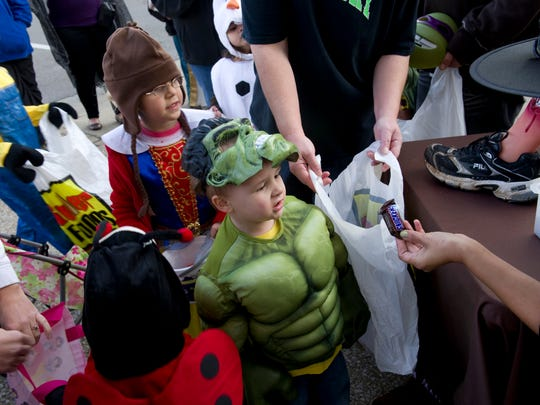 Kayden Alexander of Henderson bags a Snickers candy bar at the annual Downtown Trick or Treat in 2015.