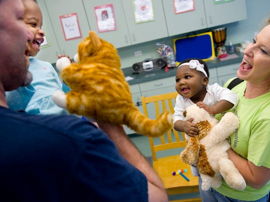 """Sisters Dania Finley, 10 months, (right) and Micaih Finley, 2, greet the cat and dog hand puppets from the book, """"The Big Fat Worm"""" with their parents David and Sandy Finley at Newburgh's Central Library during a previous year's library programming. The Rockport, Ind., family is one of many who make a regular pilgrimage to the library's puppet shows, dance parties and story times."""