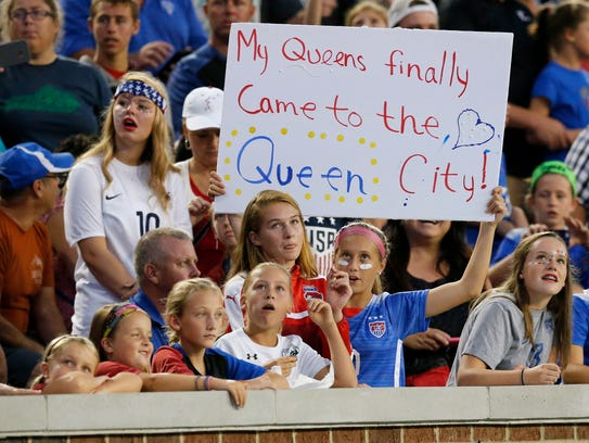 Soccer fans cheer before the first half of the international