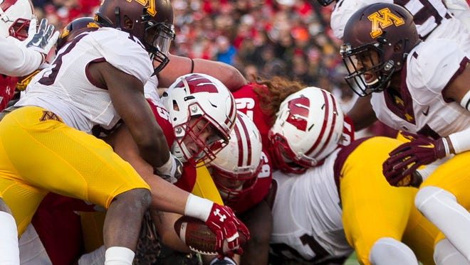 Wisconsin fullback Alec Ingold (45) scores a touchdown against Minnesota linebacker Jonathan Celestin, left, and defensive back Damarius Travis (7) during the first half of an NCAA college football game Saturday, Nov. 26, 2016, in Madison, Wis. (AP Photo/Andy Manis)