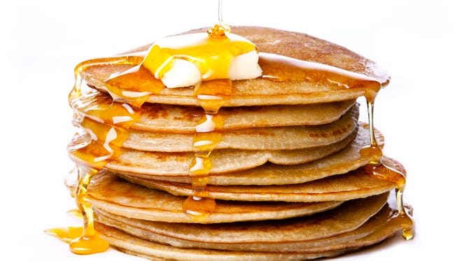 Stack of Small pancakes with butter and honey syrup on white background