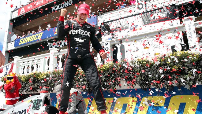 Will Power, of Australia, pumps his fist as he stands on his car and celebrates in Victory Lane after winning the Pocono IndyCar 500 auto race Monday, Aug. 22, 2016, in Long Pond, Pa.