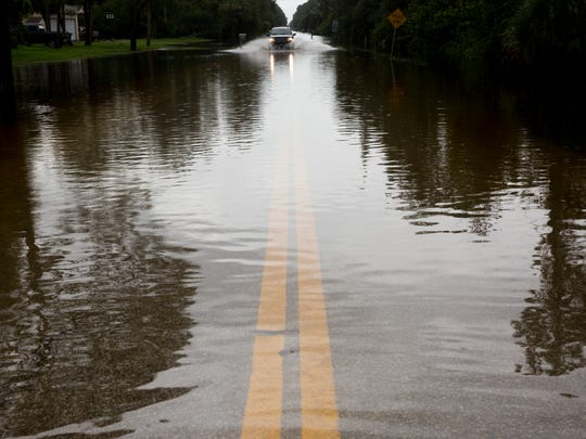A motorist drives through a flooded section of Hickory Wood Drive just off Logan Boulevard as rainfall continued throughout the day across Collier County Aug. 27, 2017, in Naples.