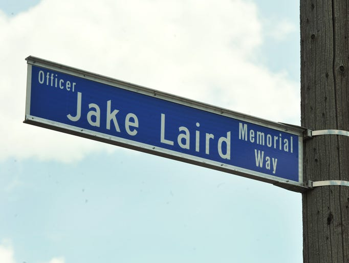 "A street sign honoring Indianapolis Metropolitan Police Department Officer Timothy ""Jake"" Laird was unveiled at a ceremony to dedicate the street in front of Southeast District headquarters Officer Jake Laird Memorial Way, Monday August 18, 2014.  Officer Timothy ""Jake"" Laird was killed in the line of duty  responding to a 911 call reporting gunfire August 18, 2004."
