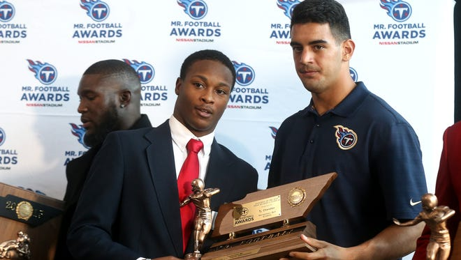 MBA's Ty Chandler, left,  accepts the Mr. Football award for Division II-AA Back of the Year, from Tennessee Titans quarterback Marcus Mariota, in 2015.