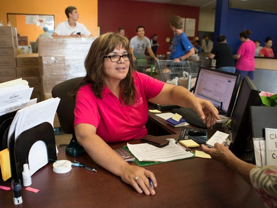 Mina Valerio works with customers at the St. Mary's Food Bank Alliance on Thursday, July 13, 2017 in Phoenix, Ariz.