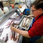 Kevin Dean, co-owner of Superior Fish Company, puts Whitefish out for sale in Royal Oak, Mich., Monday, April 14, 2014. Many fish markets in the Great Lakes region are running short of whitefish, and it's coming at a bad time: Passover. The shortfall is yet another ripple effect of the bitterly cold winter that caused vast sections of the Great Lakes to freeze over. Dean said his latest shipment of Whitefish amounted to just 75 pounds although he requested 500. (AP Photo/Paul Sancya)