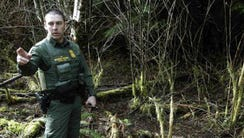 U.S. Border Patrol Agent Chris Dyer stands in a forested