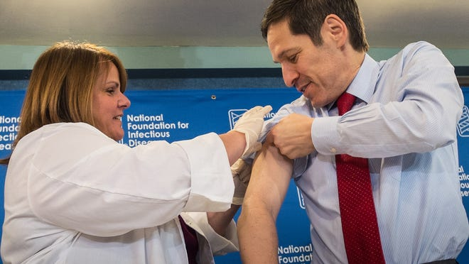 "Dr. Thomas Frieden, director of the Centers for Disease Control and Prevention, gets a flu shot from Sharon Bonadies at a news conference at the National Press Club in Washington<137>, Sept. 18, 2014<137>. <137>""Vaccination is the single most important step everyone 6 months of age and older can take to protect themselves and their families against influenza,"" said Frieden. Influenza hospitalized a surprisingly high number of young and middle-aged adults last winter, and this time around the government wants more of them vaccinated. (AP Photo/J. David Ake)<137>"