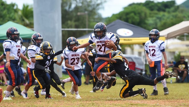 Broncos player Isaiah Ichihara (27) attempts to avoid a tackle against the Steelers in the Metgot division during their Guam National Youth Football Federation game at Hal's Angels Field on Aug. 13, 2017.