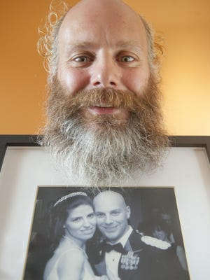 Rob Jensen of Voorhees, holding a photo of him and his wife Ardis at their December 14, 2002 wedding, decided not to shave any part of his body for the entire year so that he could raise money for Alex's Lemonade Stand to fight pediatric cancer. 08.03.15