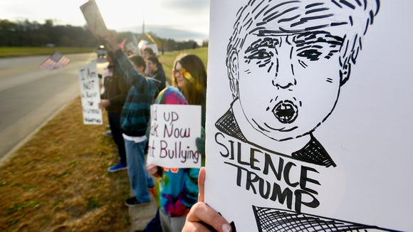 People hold signs during a silent protest of Donald