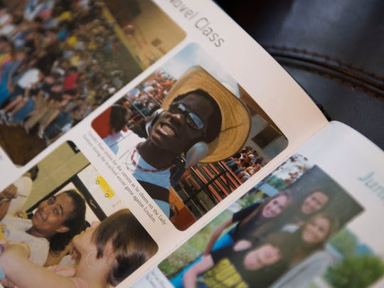 Timothy Brass shows a photo of himself in his yearbook