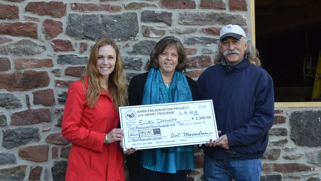 HGAC Barn Preservation Project 2015 Grant Award recipient, Ellen Dayhoff, center, receives a $2,300 check from Kendra Debany, HGAC barn preservation specialist, left, and Curt Musselman, HGAC Preservation Committee chair, right. This matching grant helped fund work to repair an unstable foundation and rotted sills on her barn.