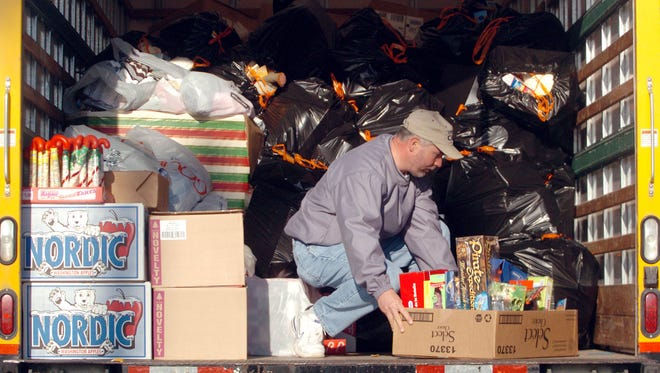 Larry Pendergraft loads the last of the toys onto a Ryder truck full of bags and boxes of toys and clothes from Tucker Realty for the Goodfellows Christmas Party in this 2006 file photo.