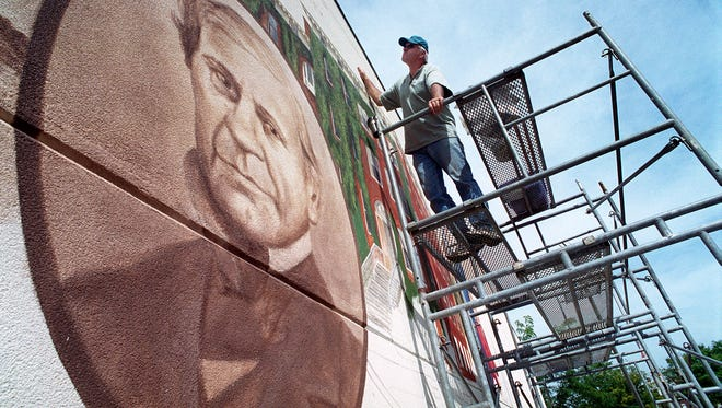 Don Gray works on a mural on the Health Center building on S. George St., portraying the past and future of the Children's Home of York. Left, the founder of the home in the year 2000.