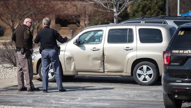 A Fond du Lac County Sheriff's deputy talks with a Wisconsin State Patrol trooper March 11 in the St.Agnes Hospital parking lot in Fond du Lac as they look over damage to a vehicle that was involved in two high speed pursuits in Dodge and Fond du Lac Counties.