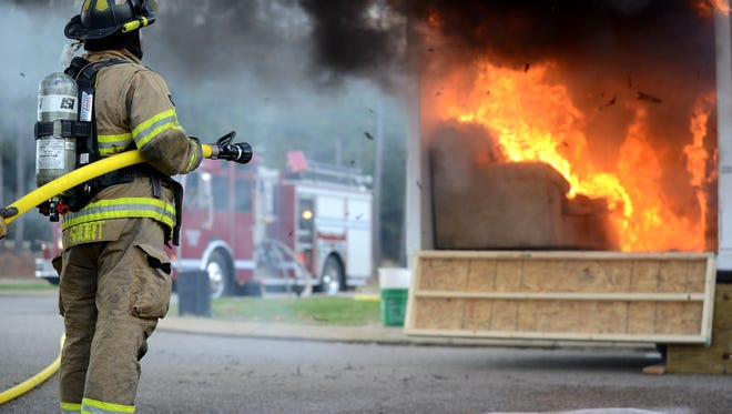 """Tim Short, a Hardin County firefighter, waits to douse the flame out on a """"room"""" not equipped with sprinklers at Hardin County High School Saturday. The activity demonstrated the benefits of having sprinklers in the home. MEGAN SMITH/The Jackson Sun"""