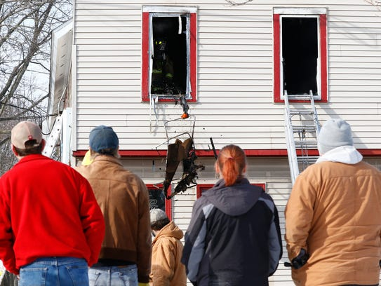 Bystanders watch a Wausau firefighter tosses out fire