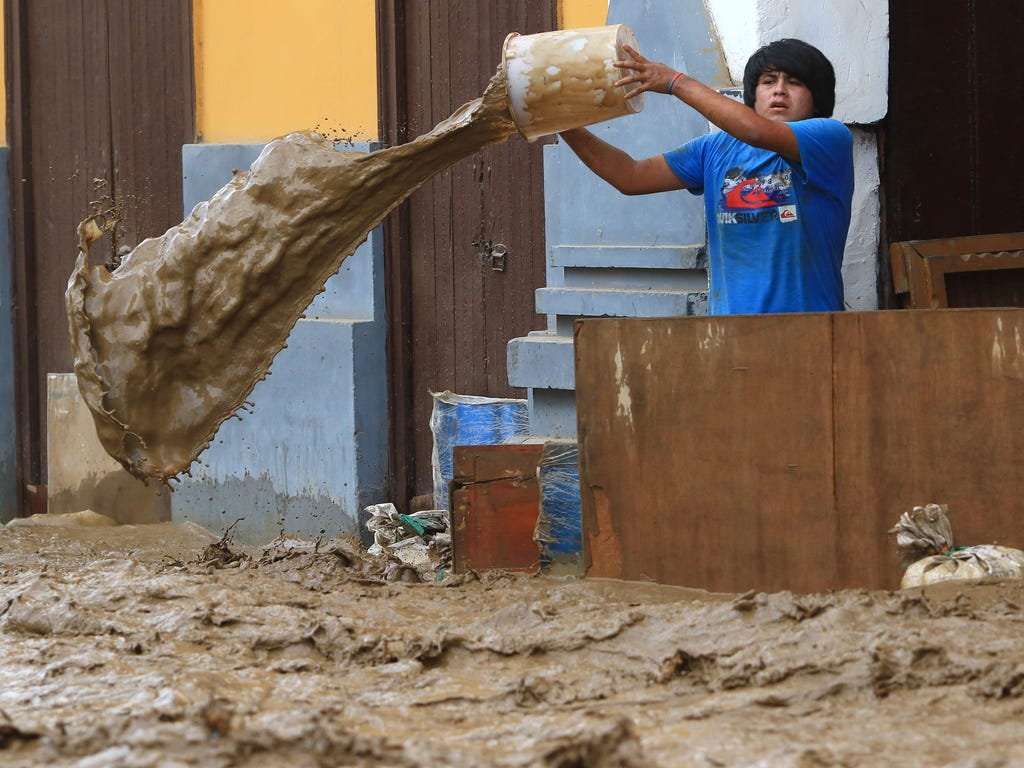 A local resident bails water from behind a barrier as a flash flood hits the city of Trujillo, 354 miles north of Lima on March 18, 2017, bringing mud and debris.\u000aThe El Nino climate phenomenon is causing muddy rivers to overflow along the entir