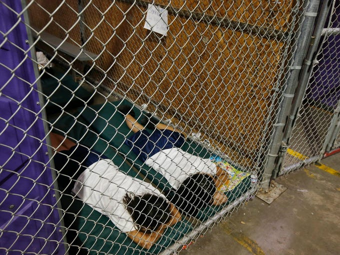 Two female detainees sleep in a holding cell at U.S.