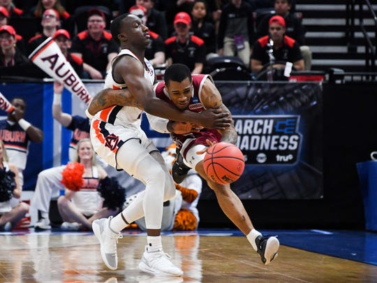 Auburn guard Jared Harper fouls New Mexico State guard AJ Harris in the first round of the NCAA Tournament on March 21, 2019, in Salt Lake City.