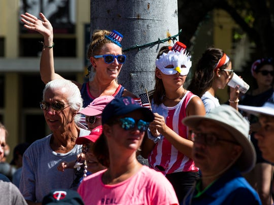 Spectators cheer and wave as floats drive by during the 4th of July Parade in downtown Naples on Wednesday, July 4, 2018.