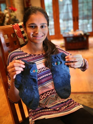 Aarya Patel, 14, shows off a pair of waterproof socks she invented at her home in Brighton, Thursday, Dec. 3, 2015.