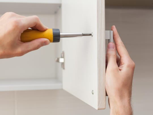 The worker sets a new handle on the white cabinet