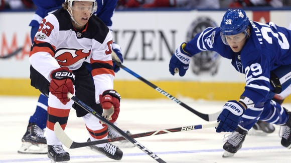 New Jersey Devils left wing Jesper Bratt (63) and Toronto Maple Leafs center William Nylander (29) battle for the puck during the first period of an NHL hockey game Wednesday, Oct. 11, 2017, in Toronto. (Nathan Denette/The Canadian Press via AP)