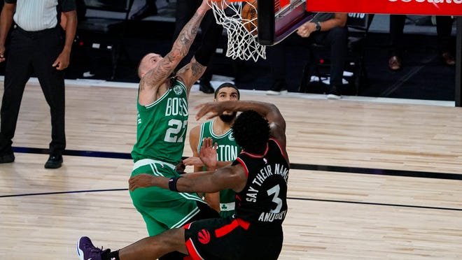 Boston Celtics center Daniel Theis (27) gets a dunk over Toronto Raptors forward OG Anunoby (3) during the second half of an NBA conference semifinal playoff basketball game Wednesday, Sept. 9, 2020, in Lake Buena Vista, Fla.