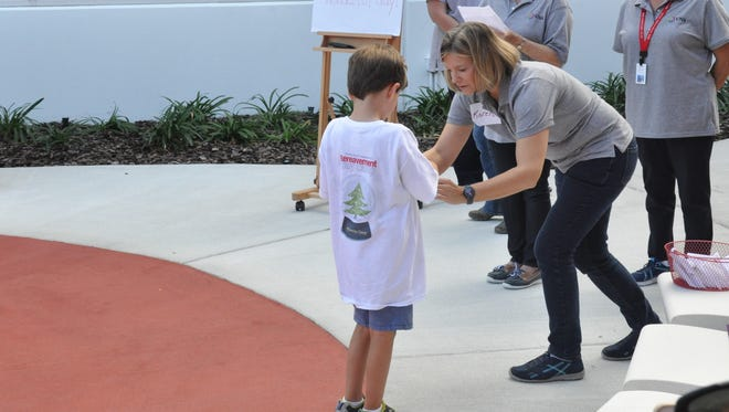VNA staff helps camper during butterfly release,