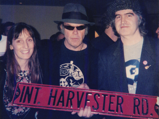 Neil Young poses with San Diego fans Devon Cronin and her husband, Ciaran, after they presented him with a pertinent street sign they found.
