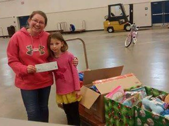 Madelynn Cooley delivers four boxes of toys and money she collected to Salvation Army Capt. Telinda Wilson at the Fairgrounds for Dec. 14 distribution to families in need of Christmas help. Pictured are Wilson, left, and Cooley.