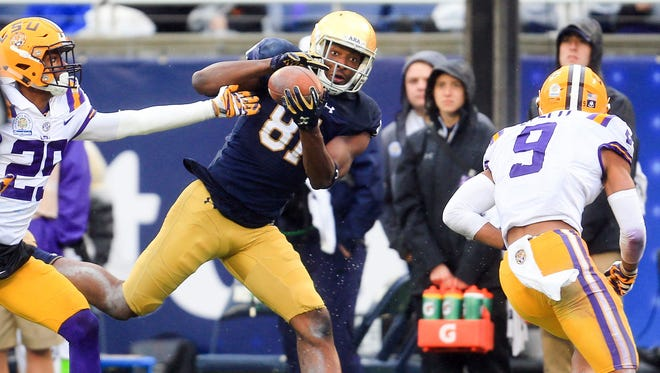 Jan 1, 2018; Orlando, FL, USA; Notre Dame Fighting Irish wide receiver Miles Boykin (81) makes a catch in front of LSU Tigers cornerback Andraez Williams (29) during the second half in the 2018 Citrus Bowl at Camping World Stadium.