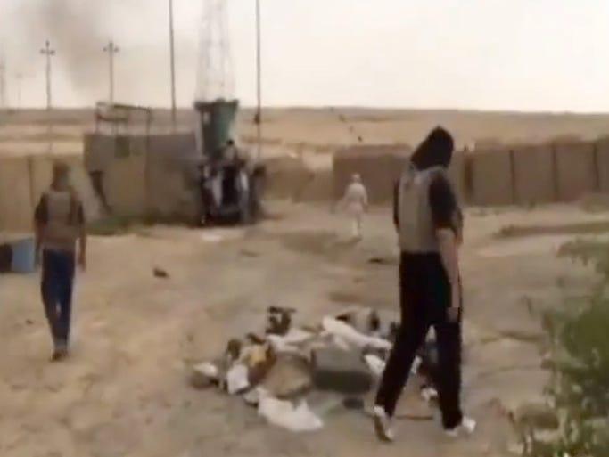 Militants walk through the captured Al-Sharqat military base.