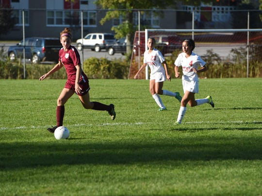 Arlington's Michaela Fasalino, left, takes the ball down field as Ketcham's Emily Castro, right, trails behind.