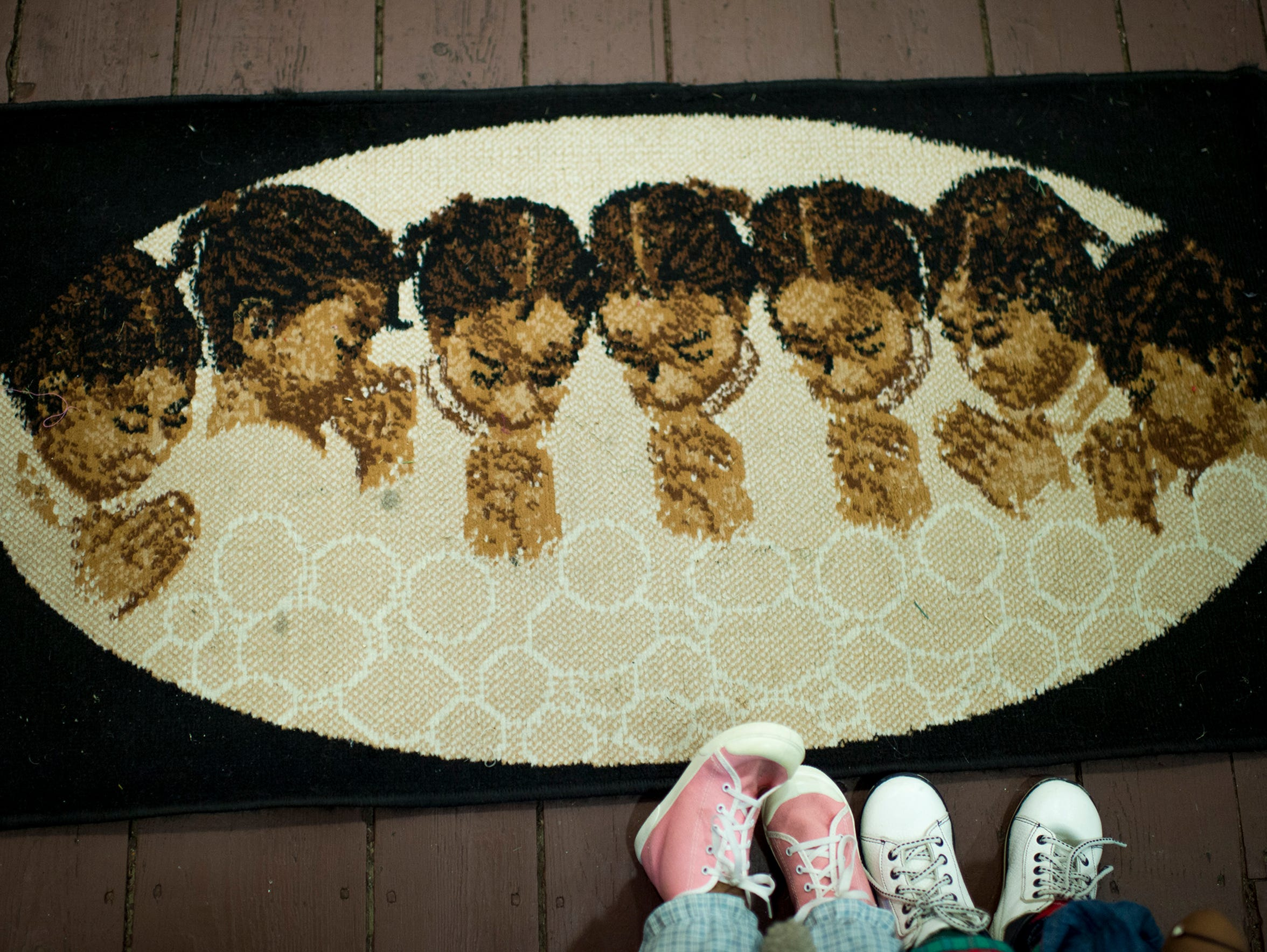 Dolls' feet are seen at the edge of a carpet inside