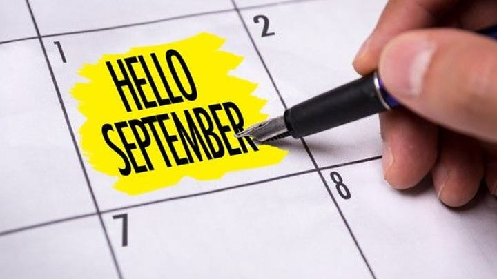 """Hand holding pen next to words """"Hello September"""" highlighted in yellow on calendar"""