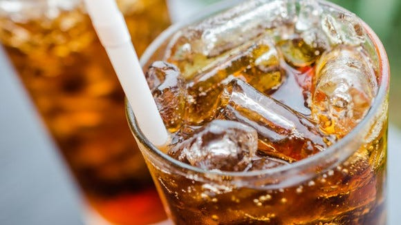 Close-up of a glass of cola with ice and a straw in it