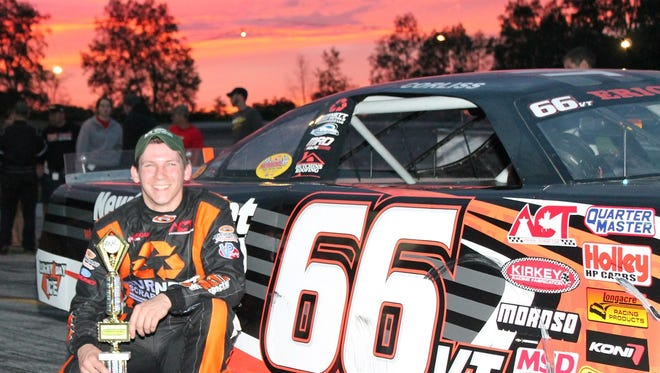Jason Corliss of Barre celebrates his victory in the North Country Federal Credit Union 50 at Thunder Road before a glowing sunset on Thursday night.