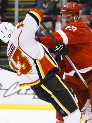 Detroit Red Wings defenseman Jonathan Ericsson, right, roughs up a Calgary Flames opponent in 2013.