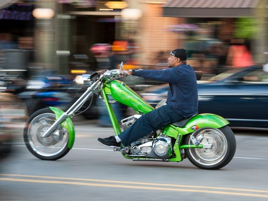 A motorcyclist cruises along Main Street in downtown