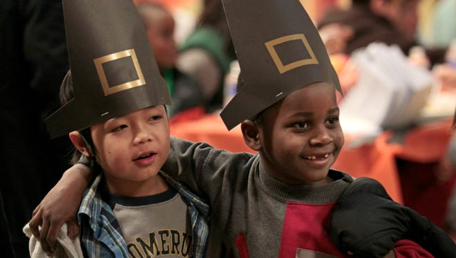 New best Pilgrim pals second grader Kae Doh Soe, a native of Thailand, left, and first grader Pierre Baraka, a native of the Republic of Congo, are all smiles and laughs as they walk through the crowded cafeteria sporting their pilgrim hats made in art class, at the Rochester International Academy's 5th annual Thanksgiving Dinner held at the school Monday, Nov. 23, 2015.   The event has gotten so big, the school held two separate seatings for their students and their families.