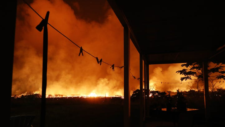 Lava from a Kilauea volcano fissure erupts and burns
