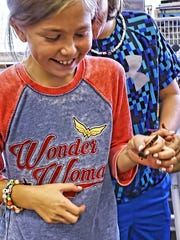 Fifth-grader Ruby Bierman affixes a tracking tag to